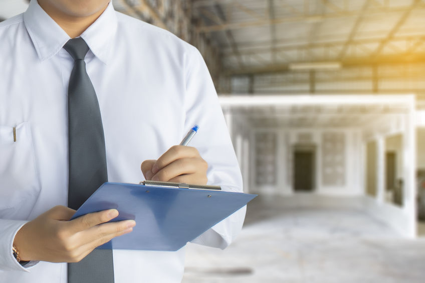 Male engineer inspection writing in factory With note on notepad